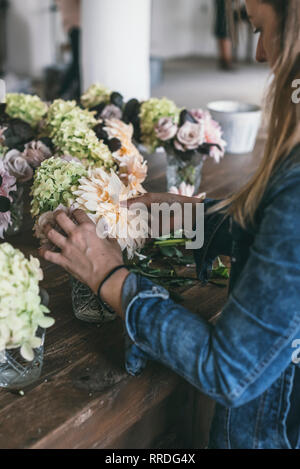 Heureux dame près de table en bois avec des bouquets de roses, chrysanthèmes frais et des brindilles de plantes en pot sur fond gris