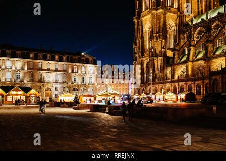 STRASBOURG, FRANCE - NOV 29, 2017: endroit majestueux de château illuminé avec Notre-Dame de la cathédrale de Strasbourg au crépuscule lors de Marché de Noël avec les piétons découvrir le lieu Banque D'Images