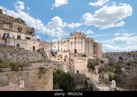 Le couvent de Saint Agostino assis sur une falaise abrupte surplombant un canyon profond ravin rempli de grottes préhistoriques de sassi de Matera, Italie. Banque D'Images