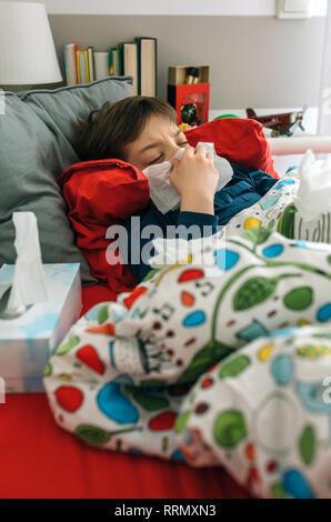 L'enfant froid allongé sur le lit Banque D'Images