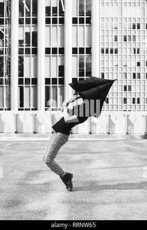 Man avec parapluie couvrant head Banque D'Images