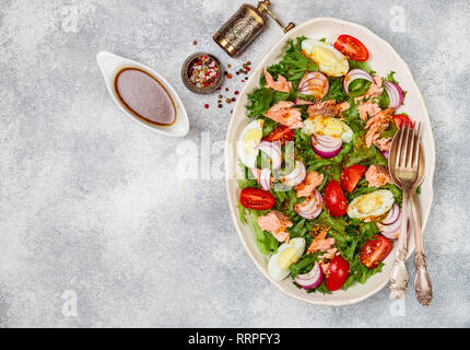 Charcuterie fraîche salade de saumon (truite) de laitue, tomates, oeufs et oignons rouges avec la moutarde et l'huile d'olive dans une assiette blanche. F sélective Banque D'Images