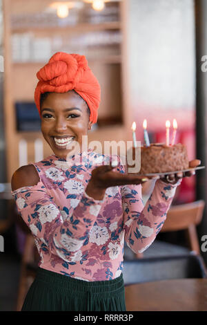 Confiant Portrait young woman holding birthday cake Banque D'Images