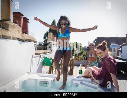 Les jeunes femmes sans souci les amis en bikini au bain à remous sur le toit Banque D'Images