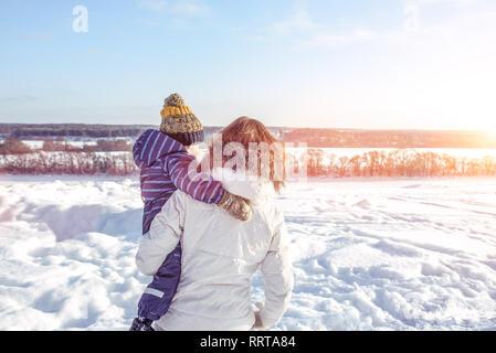 Maman avec son fils dans ses bras afin de l'arrière à l'hiver dans la ville. Les soins et l'appui d'un petit enfant à l'air libre. Dans le contexte de