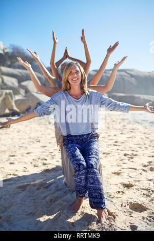 Portrait heureux classe de yoga avec bras tendus derrière femme sur sunny beach au cours de yoga retreat Banque D'Images