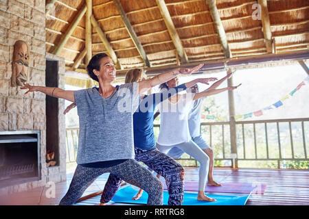 Happy woman practicing yoga guerrier 2 poser dans hut au cours de yoga retreat Banque D'Images