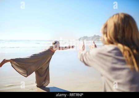Woman practicing warrior 3 poser sur plage ensoleillée au cours de yoga retreat Banque D'Images