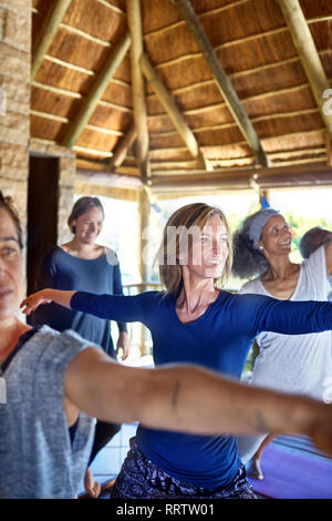 Certain woman practicing warrior 2 poser dans hut au cours de yoga retreat Banque D'Images
