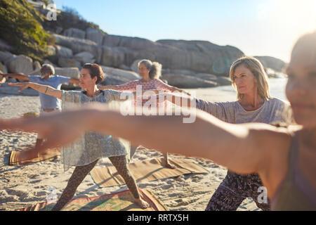 Group practicing yoga on sunny beach au cours de yoga retreat Banque D'Images