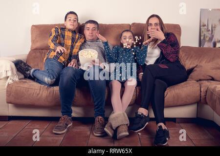 Regarder un film d'horreur de la famille sur le canapé à la maison Banque D'Images