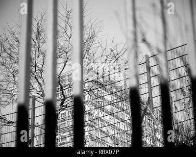 Abstraite de bâtiment d'affaires vu à travers les clôtures de sécurité - noir et blanc Banque D'Images