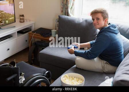 Portrait confiant young woman playing video game sur canapé à côté de fauteuil roulant Banque D'Images