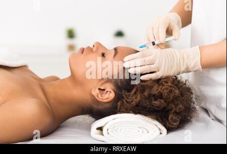 La chirurgie esthétique. Femme d'injection sur le front