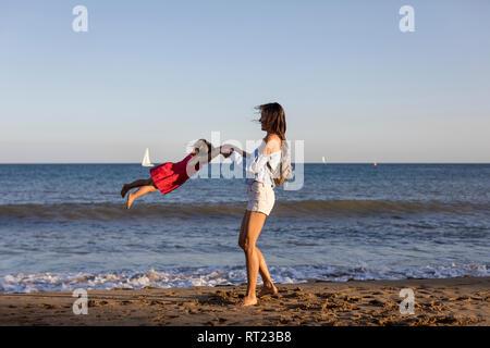 Mère et fille s'amusant sur la plage, en faisant semblant de voler