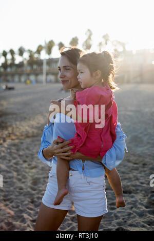 Mère et fille debout sur la plage au coucher du soleil