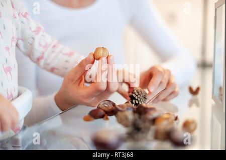 Close-up de mère et fille bricoler avec décoration d'automne à la maison Banque D'Images