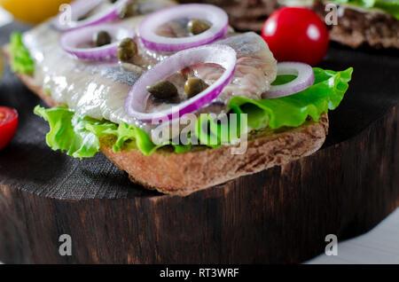 Filet de hareng avec sel, poivre, herbes, l'oignon et de citron sur la plaque noire sur fond blanc. Vue de dessus de la nourriture saine. Banque D'Images