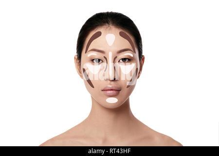 Des contours. Femme asiatique maquillage visage sur fond blanc. Contour et mettez en surbrillance le maquillage. Le visage professionnel échantillon Banque D'Images