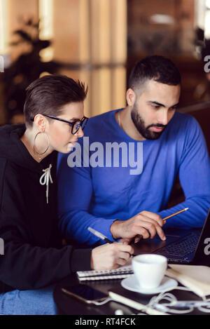 Pensive teen les élèves qui étudient avec café et coffre à la cafétéria Banque D'Images