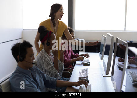 Au cours de la femme au bureau de l'ordinateur personnel Banque D'Images