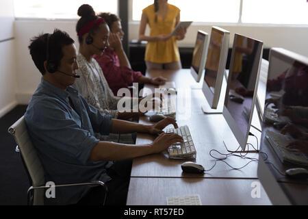Cadres travaillant sur ordinateur personnel tout en parlant sur le casque in office