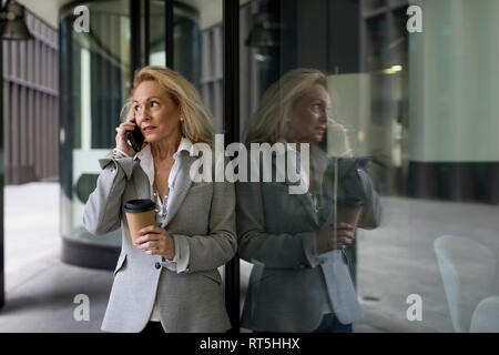 Senior businesswoman leaning against glass/talking on cell phone Banque D'Images