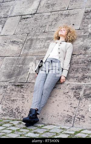 Femme blonde à la mode dossier avec leaning against wall ayant un reste
