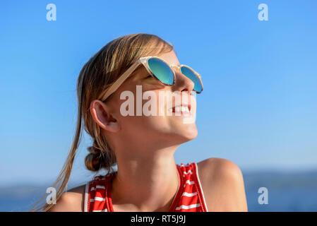 Croatie, Trogir, portrait de jeune fille de soleil sur la plage le port de lunettes de soleil Banque D'Images