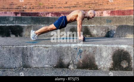 Homme musclé torse nu faisant push-ups à l'extérieur
