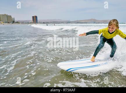 Le Chili, Arica, happy boy surf dans la mer Banque D'Images
