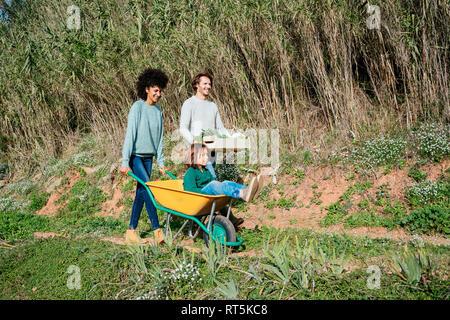 Balades en famille sur un chemin de terre, pushing wheelbarrow, exerçant son activité sous caisse à légumes Banque D'Images