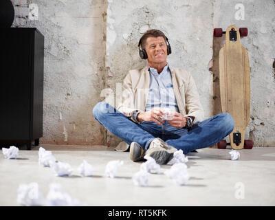 Smiling businessman sitting on office marbre d'écouter de la musique Banque D'Images