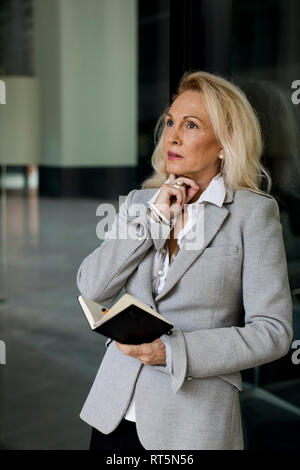Senior businesswoman leaning against glass/holding diary Banque D'Images