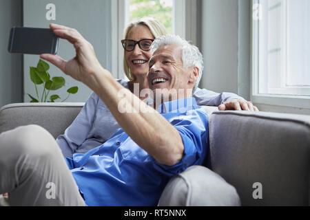 Senior couple sitting on couch à la maison à un selfies