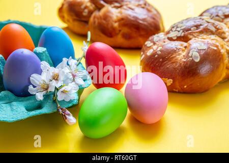 Œufs de Pâques et tsoureki tresse, pain sucré de Pâques grecque, sur un fond de couleur jaune