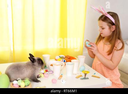 Cute little girl wearing Bunny Ears et les peintures à l'intérieur des oeufs de Pâques Banque D'Images