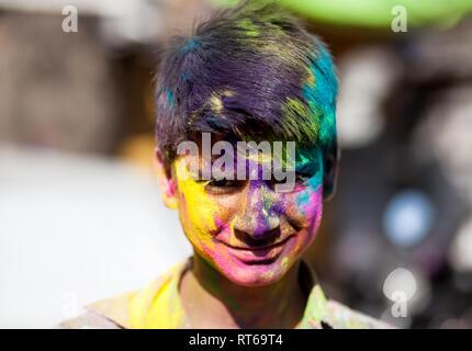 Udaipur, Inde - 6 mars 2015: Portrait de jeune Indien avec visage peint célébrant le festival haut en couleurs de Holi dans la rue. Banque D'Images