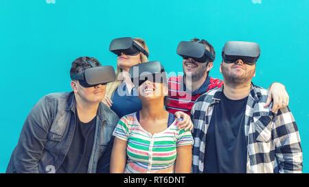 Groupe multiracial d'amis jouant les jeux de réalité virtuelle sur l'intérieur des lunettes vr