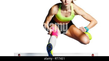 Jeunes femmes athlètes sautant obstacle au sprint. Sprinter sautant obstacle isolé sur fond blanc Banque D'Images