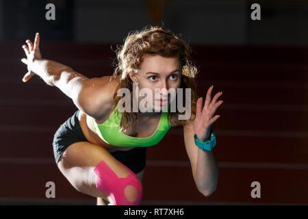 À partir de l'athlète féminine de la course sprint à partir de blocs en cours d'exécution sur fond noir Banque D'Images