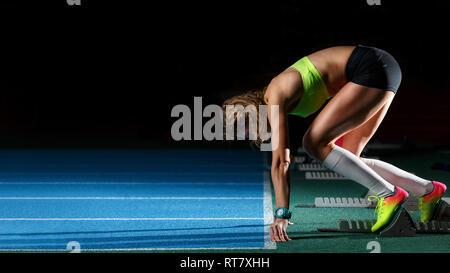 Athlète féminin sur les starting-blocks chez sprint d'exécution. Les jeunes de la sportive préparation à commencer Banque D'Images