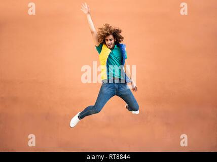 Heureux jeune homme avec les cheveux bouclés portant un gilet de sauter en l'air Banque D'Images