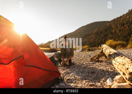Femme mature camping à Riverside, la collecte du bois pour feu de camp