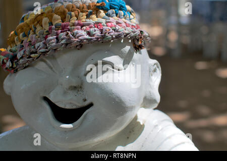 Photo d'une statue de porcelaine de rire qui porte un bonnet coloré dans la région de Sanur, Indonésie (Bali) Banque D'Images