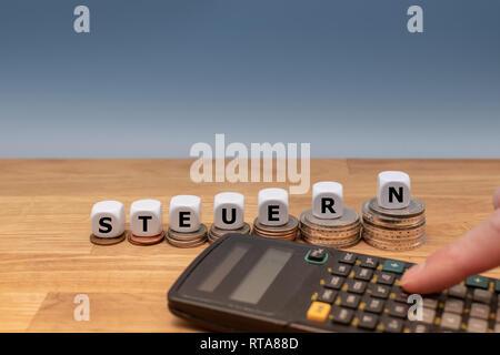 """Formulaire dés le mot allemand """"TEUERN"""" (""""taxe"""" en anglais) sur le dessus des piles de pièces. Une calculatrice de poche est à côté de la monnaie. Concept d'augmentation taxe Banque D'Images"""