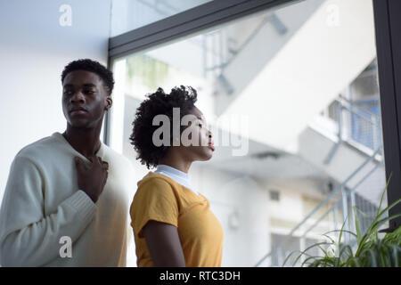Un jeune couple noir attrayant à la recherche sérieuse dans une simple chambre blanche à la mode moderne, séance photo.