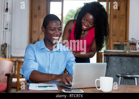 African amerian businessman at computer avec femme piscine à la maison Banque D'Images