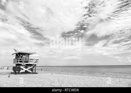 South Beach, Miami, Floride, lifeguard chambre dans un décor de style Art déco sur nuageux ciel bleu et l'océan Atlantique en arrière-plan, célèbre lieu de voyage Banque D'Images