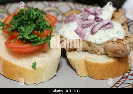 Sur une plaque sandwich vert. le porc et les légumes avec sauce tzatziki Banque D'Images